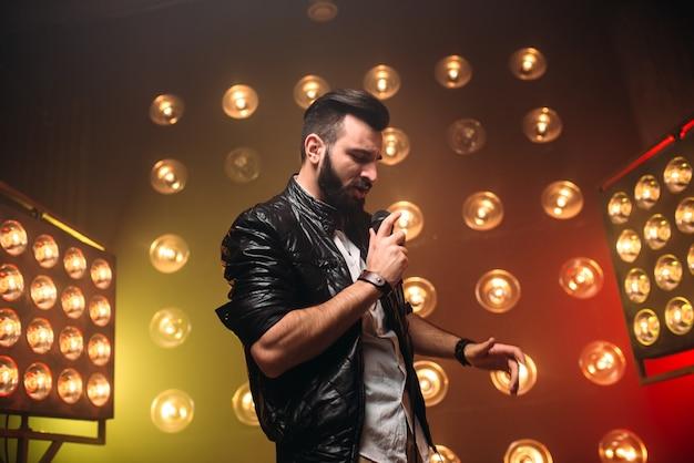 Brutale cantante barbuto con microfono canta una canzone sul palco con le decorazioni di luci