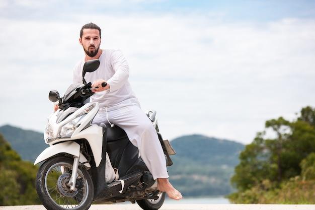 Motociclista brutale con la barba che indossa bianco seduto su una moto in montagna