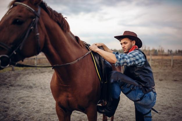 Cowboy brutale in jeans e giacca di pelle si arrampica a cavallo nel ranch del texas, western. persona di sesso maschile vintage con cavallo, selvaggio west