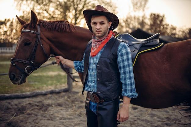 Il cowboy brutale in jeans e giacca di pelle posa con il cavallo nel ranch del texas, western. persona di sesso maschile vintage con animali, selvaggio west