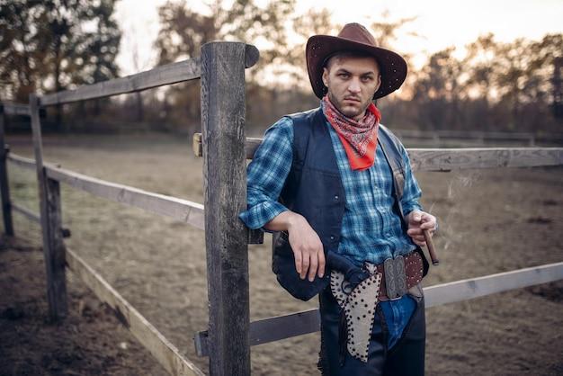 Il cowboy brutale posa nel recinto del cavallo nel ranch