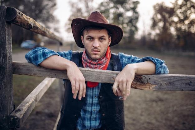 Il cowboy brutale posa nel recinto dei cavalli