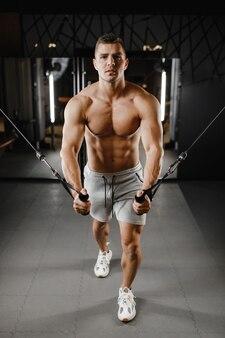Modello brutale bodybuilder con un torso nudo, si allena in palestra. concetto di allenamento pesante, fitness e bodybuilding.