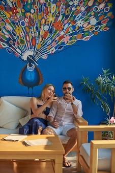 Il macho brutale si siede e si gode le vacanze con sua moglie in thailandia. dolce coppia che si diverte insieme nella moderna camera d'albergo.