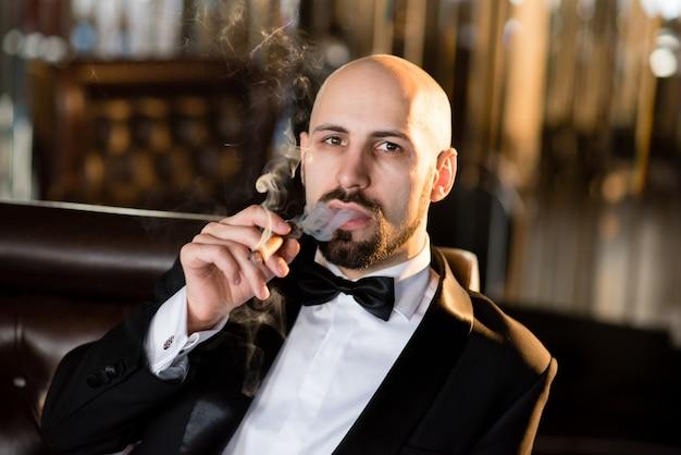Un uomo brutale con un cappotto elegante fuma un sigaro.