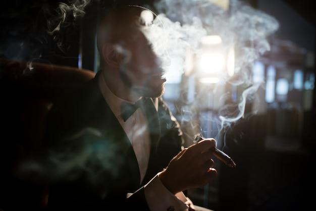 Un uomo brutale in giacca e cravatta fuma un sigaro.