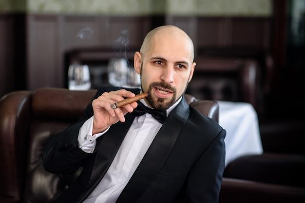 Un uomo brutale accende un sigaro.