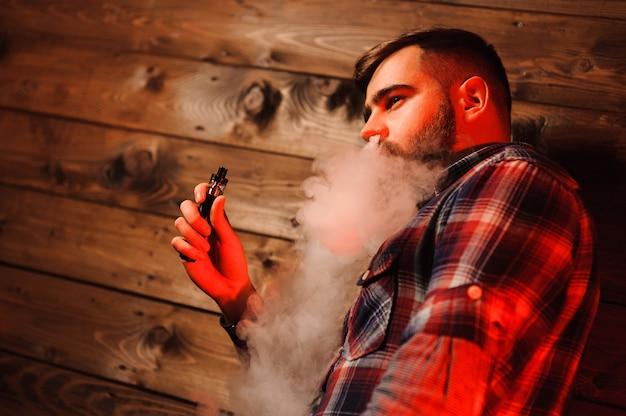 Uomo brutale che fuma sigaretta elettronica