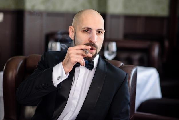 Un uomo brutale in abito fuma un sigaro.