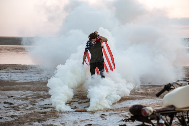 Uomo brutale che indossa mantello bandiera usa in posa in fumo bianco all'aperto