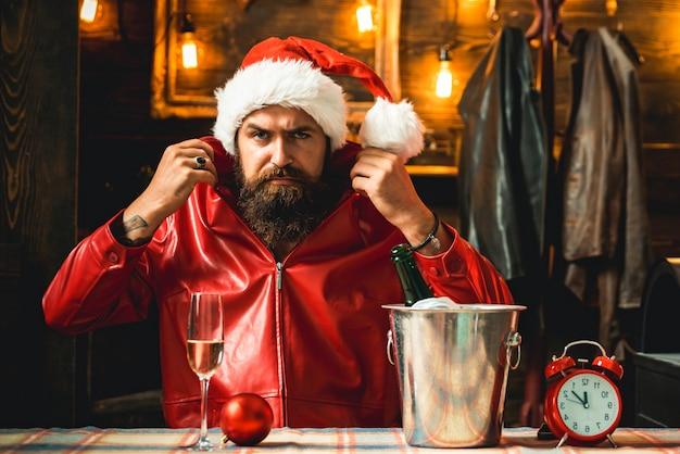 Brutale uomo barbuto di babbo natale con orologio e champagne che si prepara a incontrare il nuovo anno