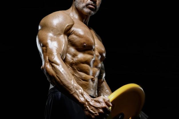 Uomo atletico brutale e muscoloso bodybuilder forte che pompa i muscoli durante l'allenamento in palestra