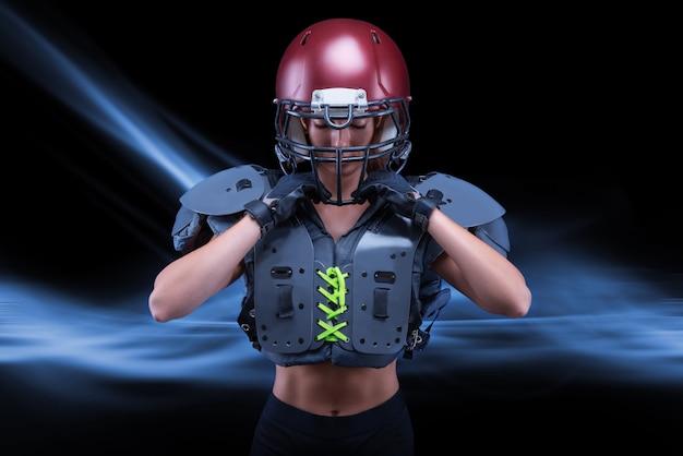 Ritratto brutale di una ragazza con l'uniforme di un giocatore di football americano. pubblicità dell'attrezzatura. concetto di sport. spalline. tecnica mista