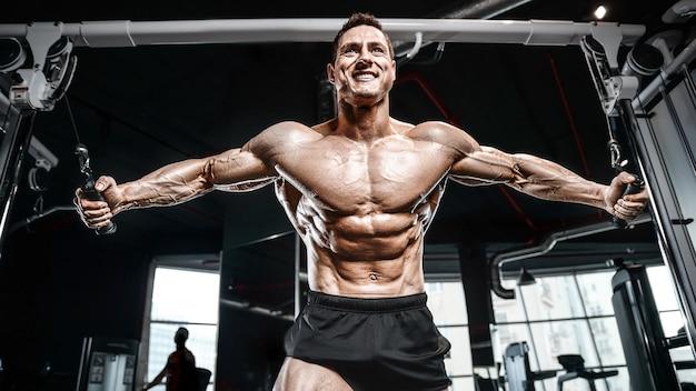 Uomo atletico brutale forte bodybuilder pompare concetto di bodybuilding allenamento muscoli