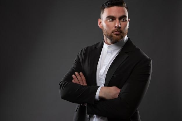 Uomo d'affari brutale con la barba lunga, vestito con un abito nero e una camicia bianca, in posa su uno sfondo scuro.
