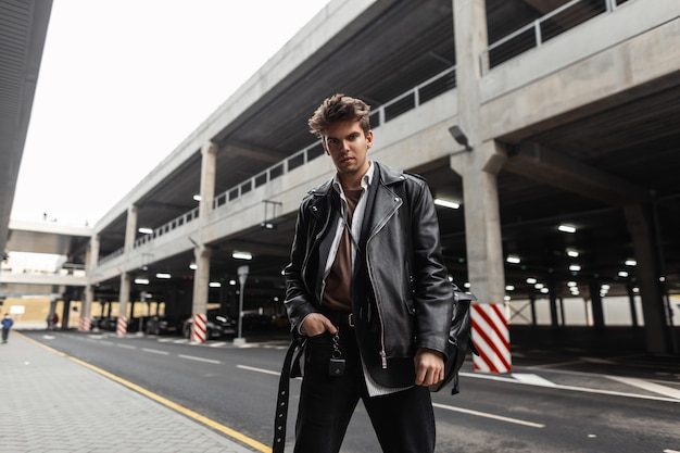 Brutale giovane hipster in abbigliamento casual nero alla moda in posa in città vicino alla strada. elegante modello urbano moderno in una giacca di pelle vintage oversize in pantaloni all'aperto. moda americana di strada