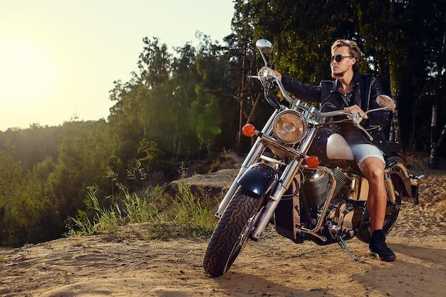 Giovane brutale in occhiali da sole, blue jeans e una giacca di pelle nera che si siede sulla motocicletta personalizzata all'aperto