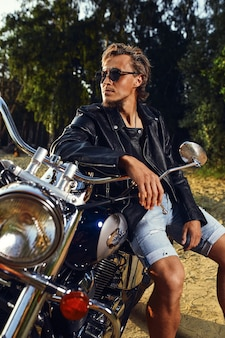 Giovane brutale in occhiali da sole, jeans blu e una giacca di pelle nera seduto sulla moto personalizzata all'aperto
