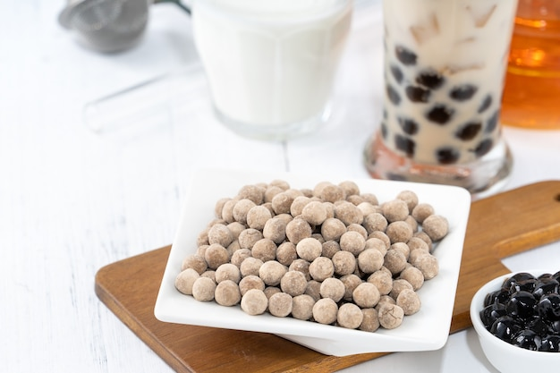 Bubble milk tea con tapioca pearl ingrediente per topping, famosa bevanda taiwanese su sfondo bianco tavolo in legno in bicchiere, primo piano, spazio copia