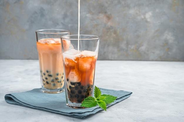 Bubble tea, che prepara una bevanda taiwanese con tapioca, latte e ghiaccio su un muro grigio. vista laterale. una bevanda rinfrescante e salutare.