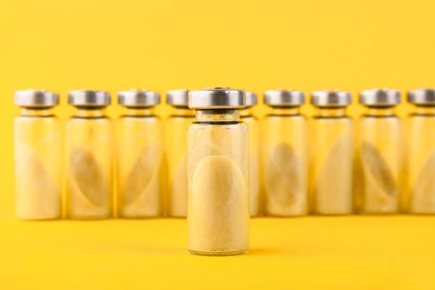Bolle, fiale con probiotico secco, bifidobatteri, con polvere probiotica all'interno su sfondo giallo. copia spazio.