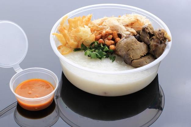 Bubur ayam o porridgew di riso indonesiano con pollo tagliuzzato. servito con kerukpuk (cracker), salsa di soia, fagioli di soia fritti e sambal. isolato su sfondo nero