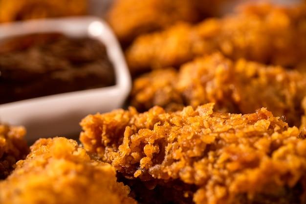 Secchio pieno di croccante pollo fritto kentucky con fumo e salsa barbecue su sfondo marrone. messa a fuoco selettiva.