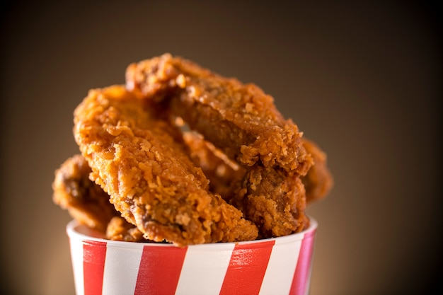 Secchio pieno di pollo fritto kentucky croccante con fumo su sfondo marrone. messa a fuoco selettiva.