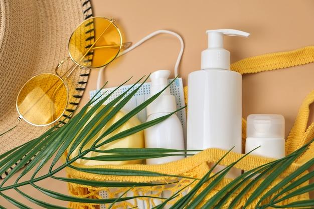 Cappello da sole a secchiello, crema solare spf in borsa a tracolla, occhiali da sole e maschera su superficie sabbia beige