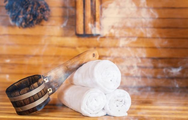 Secchio e asciugamani bianchi in sauna