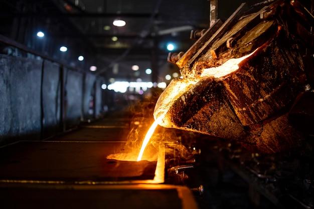 Benna con colata di ferro fuso caldo nello stampo, produzione e colata acciaio industriale, fusione, stampaggio e fonderia.