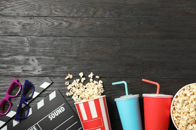 Secchi con popcorn, ciak, bicchieri e bevande su fondo di legno