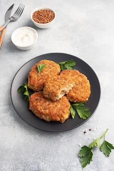 Cotolette di grano saraceno con formaggio e prezzemolo su un piatto nero su sfondo grigio chiaro