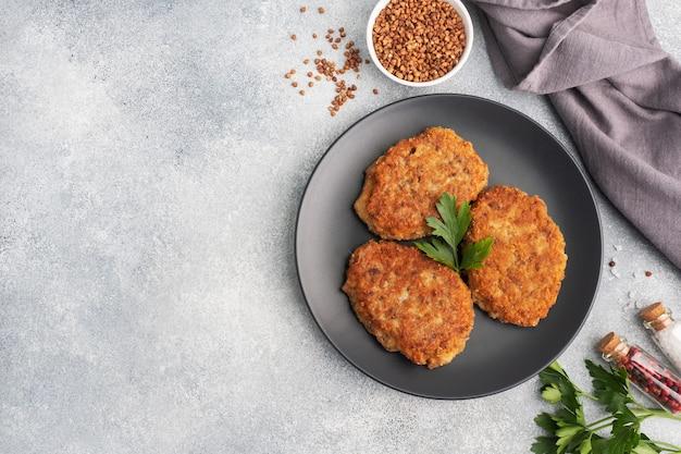 Cotolette di grano saraceno con formaggio e prezzemolo su un piatto su fondo grigio chiaro