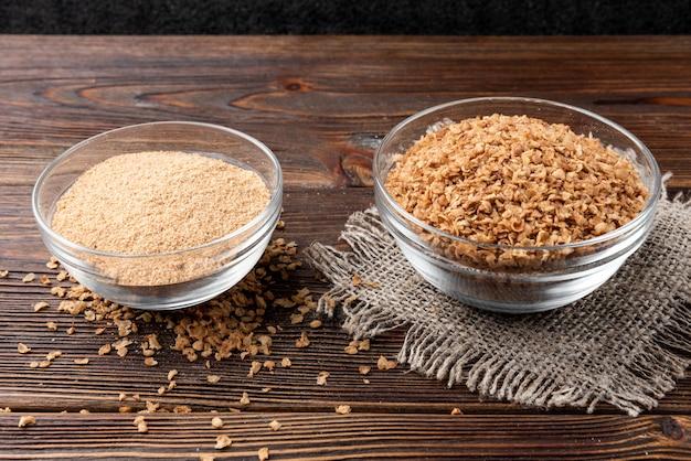 Fiocchi di grano saraceno sul tavolo di legno scuro.