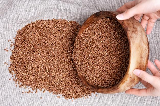 Il grano saraceno dalla ciotola di legno rotonda cade sul licenziamento. sfondo di cibo sano. grano organico naturale