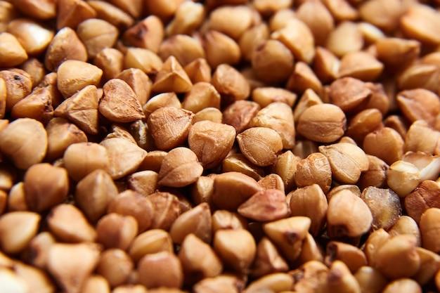 Chicchi di grano saraceno. nocciolo marrone secco come sfondo. messa a fuoco selettiva