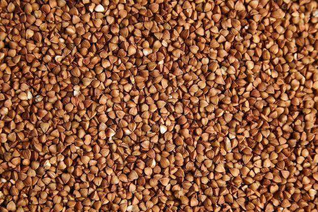Chicchi di grano saraceno. nocciolo marrone secco come sfondo