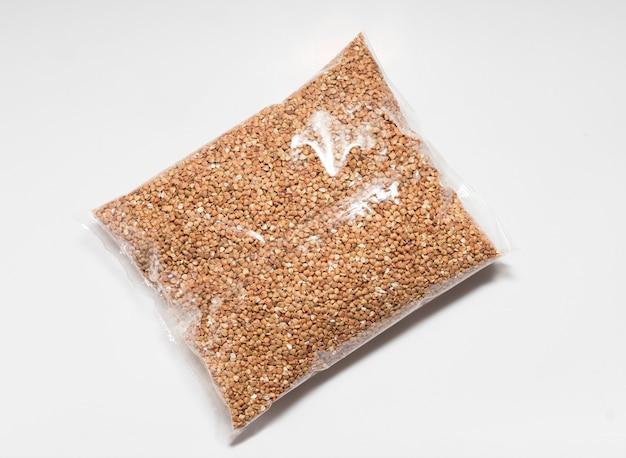 Semole di grano saraceno in un sacchetto trasparente di primo piano su uno sfondo bianco.