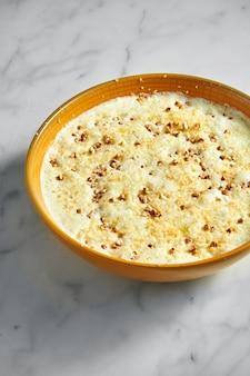 Farinata di grano saraceno cotto sul latte in una ciotola giallo brillante su marmo chiaro