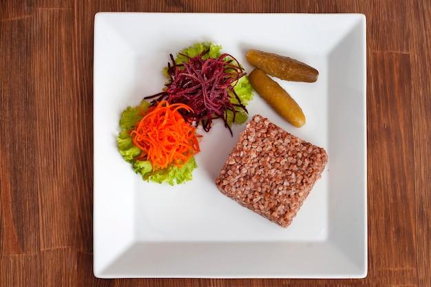 Porridge di grano saraceno con carota grattugiata, barbabietola e cetriolo sottaceto