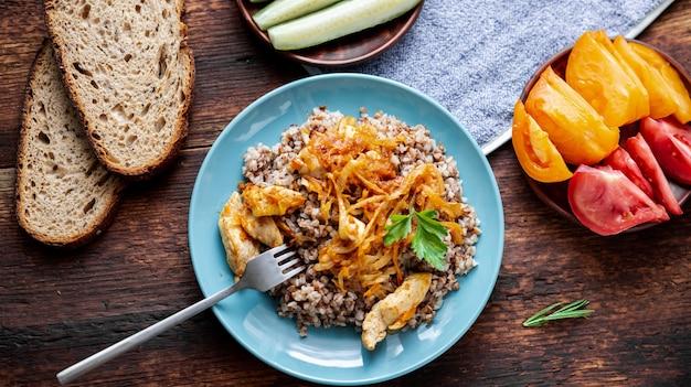 Farinata di grano saraceno con carne, cipolle e carote su un fondo di legno. con verdure fresche, cetrioli e pomodori.