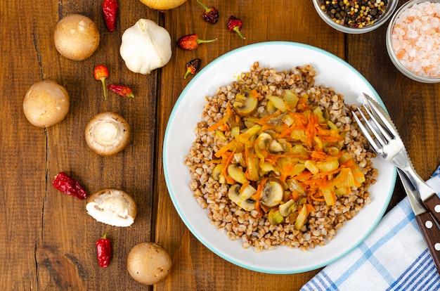 Porridge di grano saraceno con cipolle, carote e funghi.