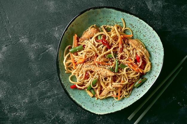 Udon wok di grano saraceno con pollo, salsa di coriandolo di verdure in un piatto verde. primo piano, messa a fuoco selettiva