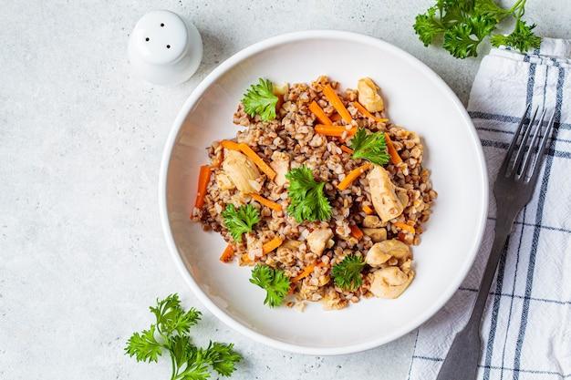 Grano saraceno con carne di pollo e verdure in un piatto bianco, sfondo bianco