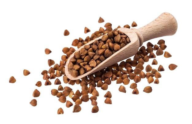 Grano saraceno in mestolo di legno isolato su bianco
