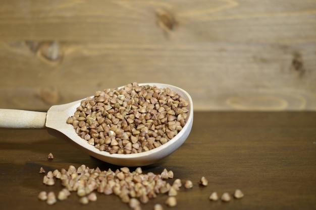 Grano saraceno in un cucchiaio di legno su un fondo di legno marrone. concetto di cibo sano. messa a fuoco selettiva