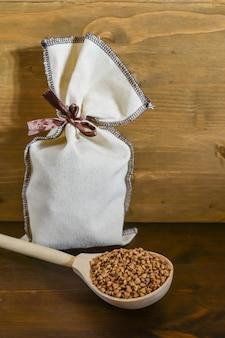 Grano saraceno in cucchiaio di legno, accanto al sacco di tela con grano su fondo di legno marrone. cibo salutare