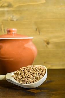 Grano saraceno in cucchiaio di legno, accanto al vaso di argilla su fondo di legno marrone. cucina tradizionale russa