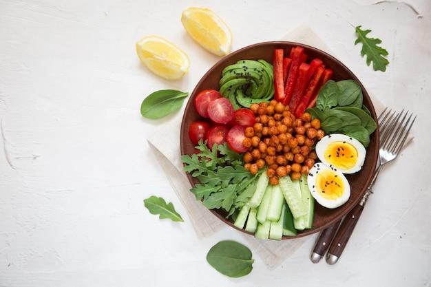 Ciotola del buddha, cibo sano ed equilibrato. ceci fritti, pomodorini, cetrioli, paprika, uova, spinaci, rucola